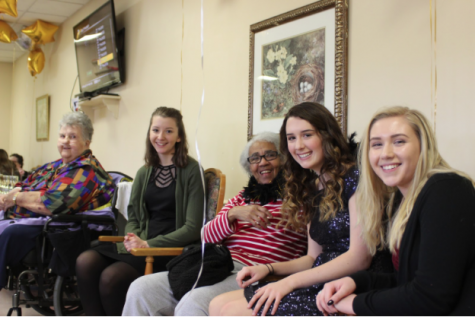 (Left to right) Arlene Dams, Sydney Klonowski, Barbara Somerville, Cassidy Holderman, and Kassidy Quick gather for a picture after singing carols together at the event. Over 25 students volunteered for the event. Students helped decorate the Center with balloons and then mingled with the residents during the Prom.